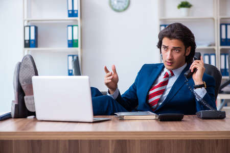Young male businessman working in the office Stock fotó - 129923299
