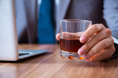 Male employee drinking alcohol and smoking cigarettes at workpla Stock fotó