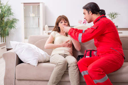 Young male paramedic visiting young woman 写真素材 - 129923480