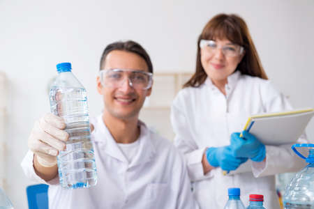 Two chemists working in the lab Фото со стока
