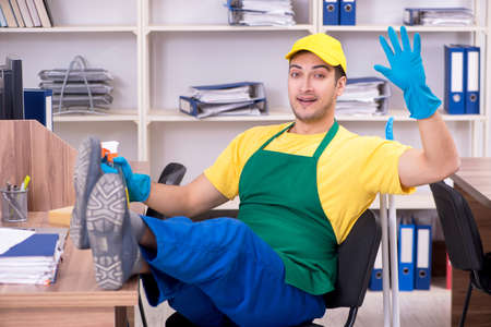 Young male contractor cleaning the office Фото со стока - 129923624