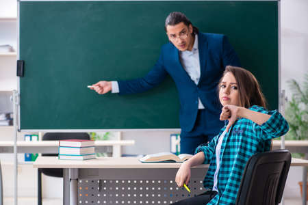 Young handsome teacher and female student in the classroom