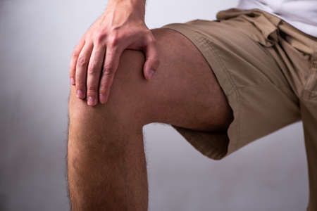 Young man suffering from leg pain