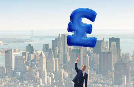 Businessman flying on british pound sign inflatable balloon Stock Photo