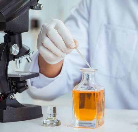 Químico mezclando perfumes en el laboratorio.
