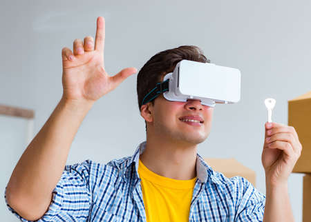 Young man wearing VR glasses moving in new apartment Stockfoto