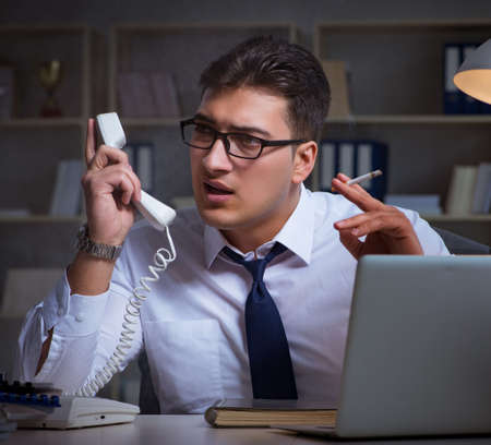 Businessman speaking on phone and smoking in office Stock Photo