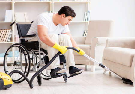 Disabled man with vacuum cleaner at home Banque d'images - 129663795