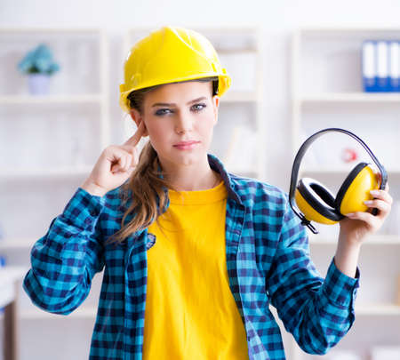 Woman in workshop with noise cancelling headphones Stockfoto