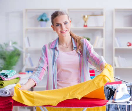 Young housewife doing laundry at home Standard-Bild - 129664294