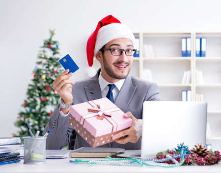 Young businessman celebrating christmas in the office Archivio Fotografico - 129664776