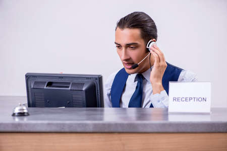 Young man receptionist at the hotel counter