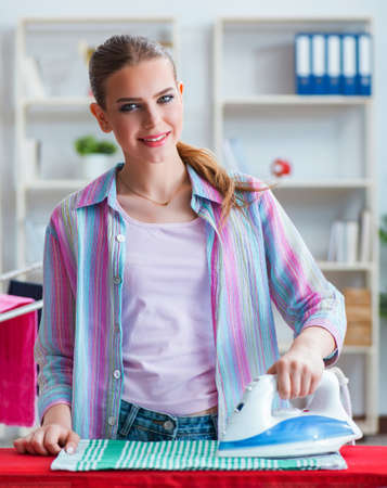 Happy housewife doing ironing at home Banque d'images - 129664820