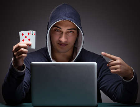 Young man wearing a hoodie sitting in front of a laptop computer Archivio Fotografico - 129664881