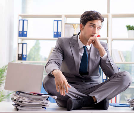 Businessman sitting on top of desk in office Stock Photo