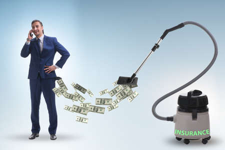 Businessman and vacuum cleaner sucking money out of him