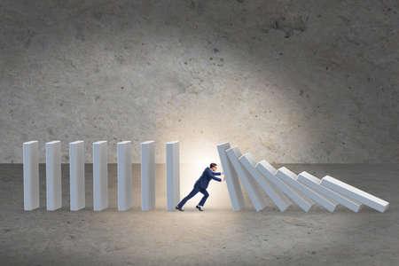 Businessman preventing domino effect in business concept Foto de archivo