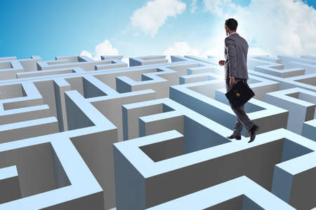 Businessman trying to escape from maze Imagens