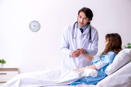 Male doctor visiting female patient in ward