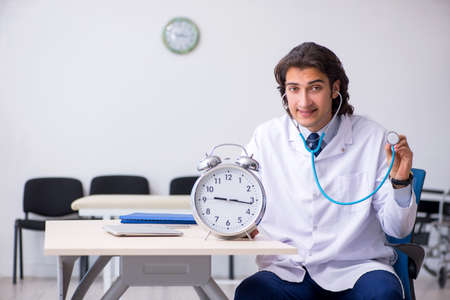 Young male doctor in time management concept Stok Fotoğraf