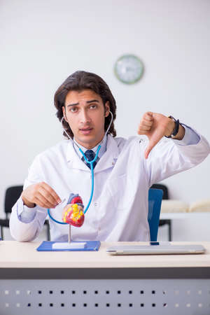 Young doctor cardiologist with heart model