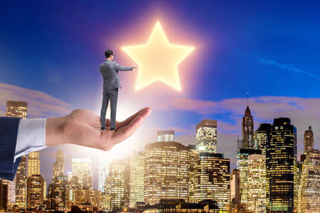 Businessman held on hand reaching out for stars
