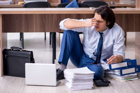 Young male employee and too many work in the office 스톡 콘텐츠