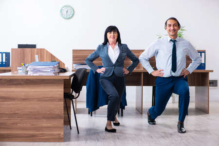 Two employees doing sport exercises in the office Stock Photo