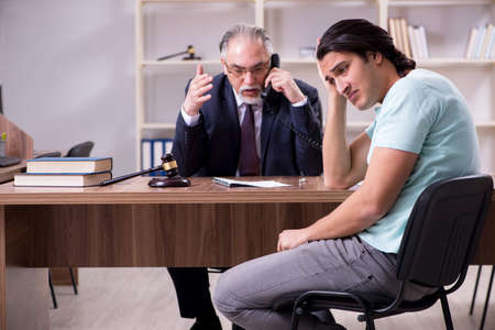 Young man visiting experienced male lawyer 스톡 콘텐츠