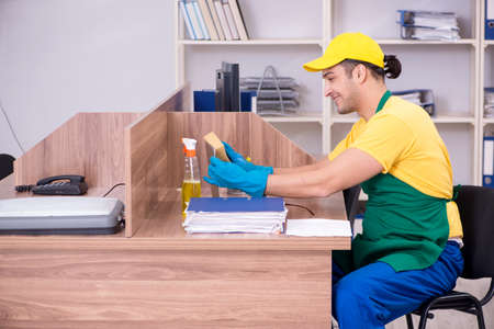 Young male contractor cleaning the office 스톡 콘텐츠
