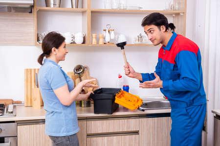 Young male repairman repairing tap