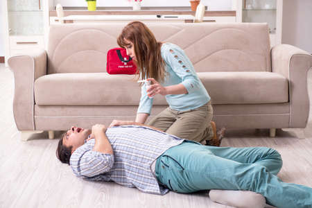 Young couple in first aid concept at home 写真素材 - 129856802