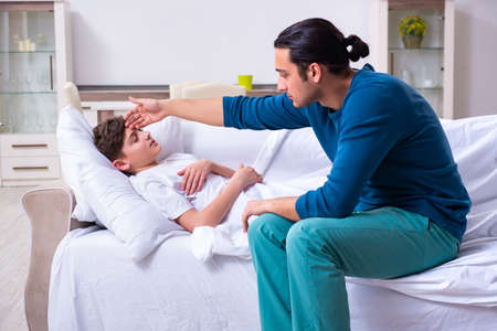 Young father caring for sick son 스톡 콘텐츠