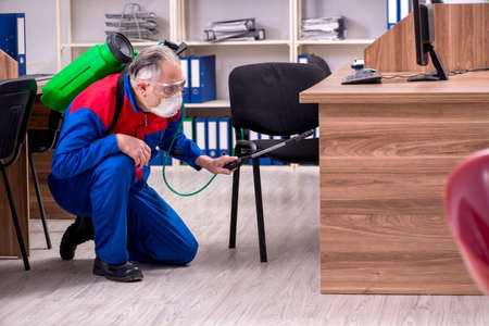 Old professional contractor doing pest control in the office Stock Photo