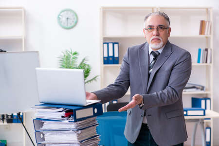 Aged male employee unhappy with excessive work 스톡 콘텐츠