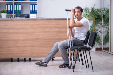 Young man at hospital reception desk Stock Photo