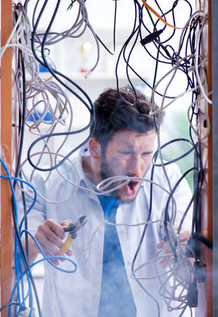 Electrician trying to untangle wires in repair concept 写真素材