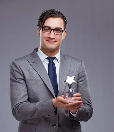 Businessman holding star award in business concept