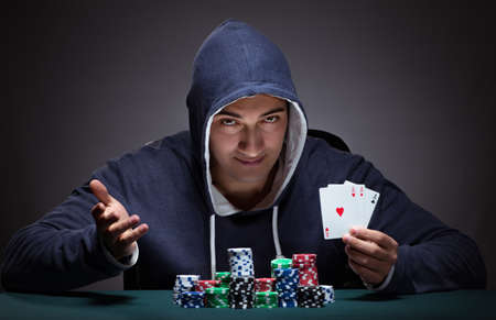 Young man wearing a hoodie with cards and chips gambling 写真素材 - 129874295