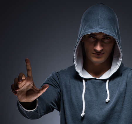 Young man wearing hoodie pressing virtual buttons