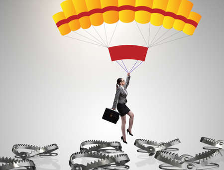 Businesswoman falling into trap on parachute 版權商用圖片