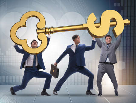Businessmen holding giant key in finance concept Фото со стока
