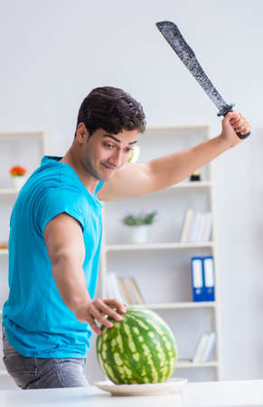 Man eating watermelon at home Imagens