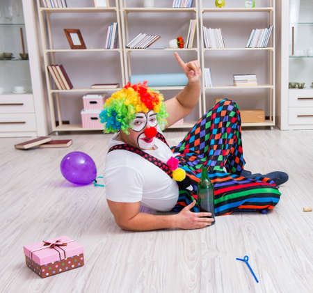 Drunk clown celebrating having a party at home 스톡 콘텐츠
