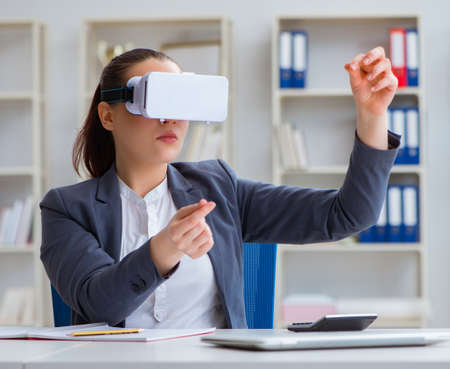 Businesswoman with virtual reality glasses in office 写真素材 - 129991010