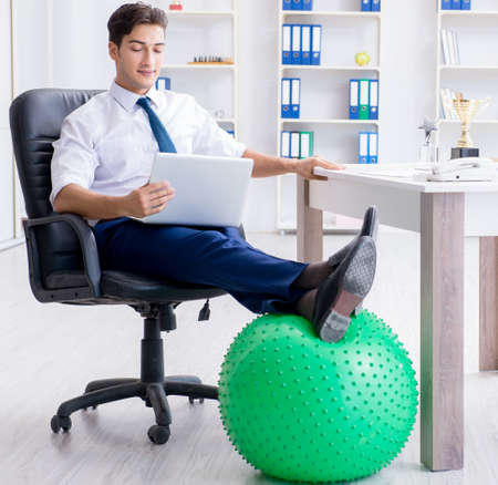 Young businessman doing sports stretching at workplace Stockfoto