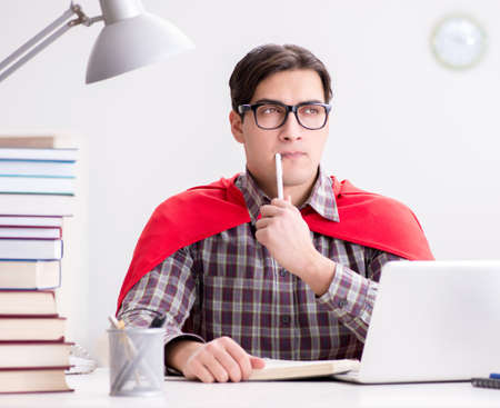 Super hero student with a laptop studying preparing for exams Фото со стока