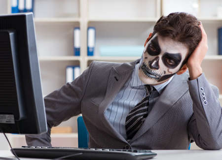Businessmsn with scary face mask working in office Imagens