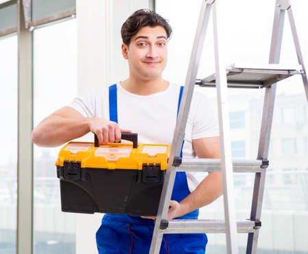 Young repairman climbing ladder at construction site