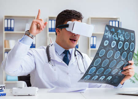 Young doctor looking at MRI scan through VR glasses 写真素材 - 129990566